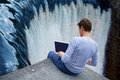 Man + notebook sitting over the waterfall Stock Image