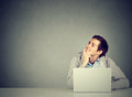 Man in office, sitting at desk with laptop daydreaming, smiling Royalty Free Stock Photo