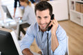 Man in office talking on phone smiling worker the Stock Image