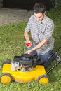 Man oiling yellow lawn mower Stock Photography