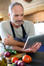 Man in old kitchen looking for recipe on internet mature reading tablet Royalty Free Stock Photography