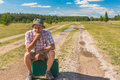 Man with old suitcase sitting on an country road and thinking Royalty Free Stock Photo