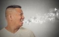 Man with open mouth blowing cold breeze snowflakes flying away Royalty Free Stock Photo