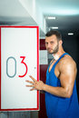 Man opens locker door in gym Royalty Free Stock Photo