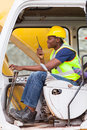 Man operates excavator afro american while using walkie talkie Stock Images