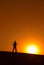 Man at orange background with big sun under horizon with heroic achievement gesture Royalty Free Stock Images