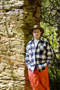 Man in Orange and Plaid on Rock Wall Royalty Free Stock Images