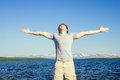 Man outdoor with his hands raised to the sky traveller standing blue northern landscape mountain and sea on background freedom and Stock Image