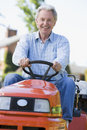 Man outdoors driving lawnmower smiling Royalty Free Stock Images