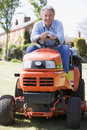 Man outdoors on lawnmower smiling Stock Image