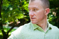 Man outside looking over shoulder a portrait of a wearing a green linen shirt outdoors Stock Photography