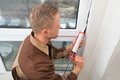 Man in overall applying silicone sealant high angle view of young Royalty Free Stock Photography