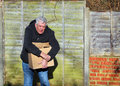 Man in pain carrying heavy box wrist strain an elderly a very the is too for him and he will cause injury to himself his is Royalty Free Stock Photography