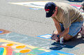 Man painting the street a actually is on rather then on paper or canvas at th chalk block event in st joseph michigan Royalty Free Stock Photo