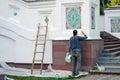 A man paints Assumption church facade.