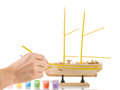 Man paints model sailing ship Stock Images