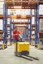 Man with pallet jack through warehouse blurred driving Royalty Free Stock Photography