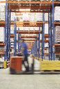 Man with pallet jack through warehouse side view of a blurred driving Royalty Free Stock Photo