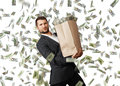Man with paper bag under dollar s rain young businessman holding heavy money Royalty Free Stock Photography