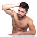Man passing his hand through his hair and looking away young naked from the camera Stock Images