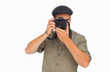 Man in peaked cap taking photo on white background Royalty Free Stock Photos