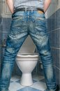 Man peeing to toilet bowl in restroom from back Royalty Free Stock Photo