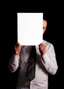 A man peeking behind empty white card shoot in low key technique Stock Images
