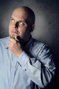 Man with pensive expression deeply thinking portrait grey textured background Stock Photos