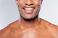Man with perfect smile cropped image of young shirtless african smiling while standing against grey background Royalty Free Stock Image