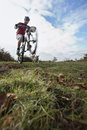 Man performing wheelie on mountain bike full length of men in countryside Stock Photography