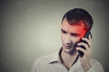 Man on the phone with headache. Cellular mobile radiation concept Royalty Free Stock Photo