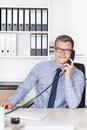 Man is phoning at the desk in the office young smiling businessman with glasses while sitting a shelf background Royalty Free Stock Image