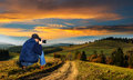 Man photographer in the mountains at sunset Royalty Free Stock Photo