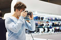 Man photographer tests digital SLR camera in shop Royalty Free Stock Photo