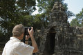 Man photographing ancient temple rear view of middle aged Royalty Free Stock Photo
