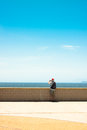 Man photographing blue sky and seascape a taking photo of over cloudless Stock Photography