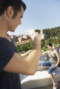 Man photographing woman sitting on stone bench young men women at barcelona Stock Photos