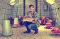 Man picking fresh eggs in chicken house
