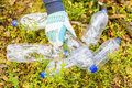 Man picking up used plastic bottles in forest Royalty Free Stock Photo