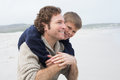 Man piggybacking his son at beach happy men cheerful the Royalty Free Stock Photos