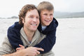 Man piggybacking his son at beach happy men cheerful the Stock Photography
