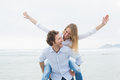Man piggybacking woman at beach cheerful young men beautiful women the Stock Image