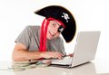 Man in pirate hat downloading music on a laptop dressed as with cd his mouth his computer and movies white background Royalty Free Stock Photo
