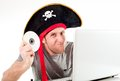 Man in pirate hat downloading music on a laptop dressed as his computer and movies white background Stock Photography