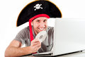 Man in pirate hat downloading music on a laptop dressed as his computer and movies white background Stock Image