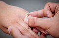 Man placing a diamond engagement ring on finger of his fiance the shallow depth field with focus the Royalty Free Stock Photo