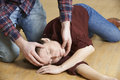 Man Placing Woman In Recovery Position After Accident