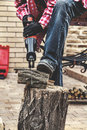 Man in plaid shirt sawing piece of wood on stump Royalty Free Stock Photo