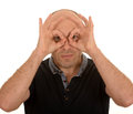 Man with in playful mood creating pretend binoculars his thumbs and fingers on a white background Royalty Free Stock Image