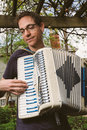 Man playing accordion outdoors hip thirty something plays a bright colorful Stock Images